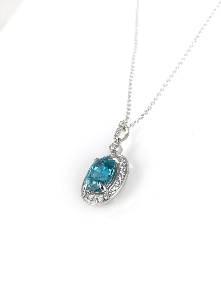 (DiamondTown) This bright pendant features a 3.09 carat oval cut blue zircon center, surrounded by a halo of round white diamonds. Additional diamonds decorate the bail, bringing the total weight to 0.26 carats.  Item details: Center: 3.09 carat