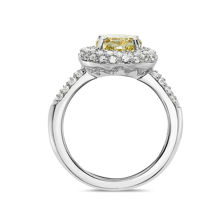 This engagement ring features a 3.09 carat VVS yellow diamond with a G-H VS diamond halo setting weighing 1.10 carats. 7.8 grams total weight. Made in Italy. Size 6 3/4.  Viewings available in our NYC showroom by appointment.