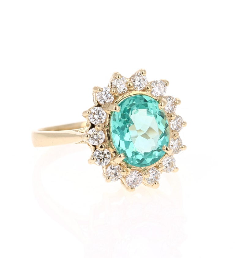 Classic and beautifully designed Apatite and Diamond Ring!   This ring has a 2.48 carat Oval Cut Apatite in the center of the ring and is surrounded by 14 Round Cut Diamonds that weigh a total of 0.62 carats.   The Clarity and Color of the Diamonds