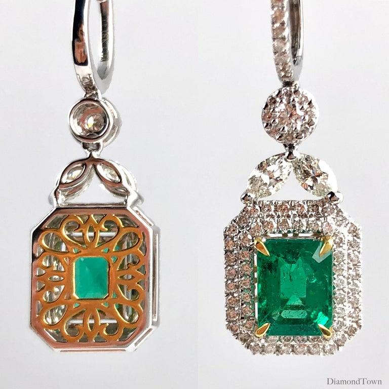 These stunning earrings feature 3.10 carats emerald cut fine emeralds, surrounded by a double halo of round white diamonds. These halos hang from a delicate flower design made of two marquise cut diamonds and another round white diamond inside its