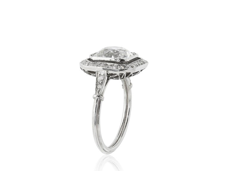 Platinum vintage style ring consisting of 1 Old European cut diamond weighing approximately 3.10 carats having a color and clarity of I/SI1 respectively, set with Old European cut diamonds surrounding the center stone and going down the shoulders