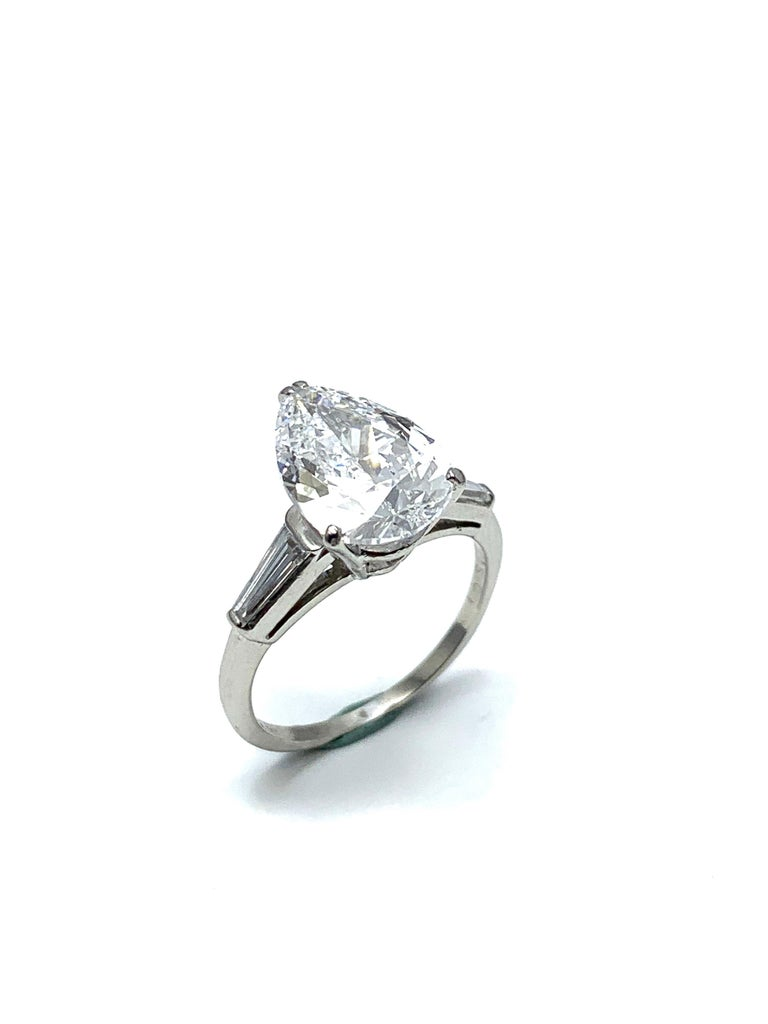 An absolutely stunning 3.14 carat pear shape Diamond and platinum ring.  The pear shape is set in a four prong basket setting, with a tapered baguette Diamond on each side tapering into the shank.  The 3.14 carat Diamond is graded by GIA as a D