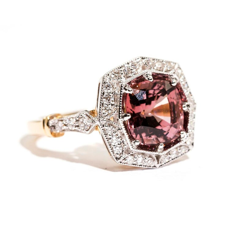 Forged in 18 carat yellow and white gold is this vintage inspired halo ring that features a striking 3.16 carat bright reddish pink cushion cut natural spinel complimented by a total of 0.31 carats of sparkling round brilliant cut diamonds. We have