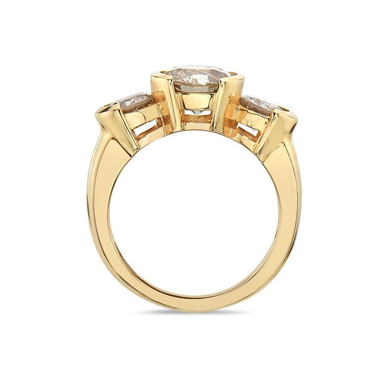 This trilogy engagement ring features a 2.02 carat top light brown SI clarity center stone. 7.6 grams total weight. Size 7 1/4.  Resizeable upon request.  Viewings available in our NYC showroom by appointment.