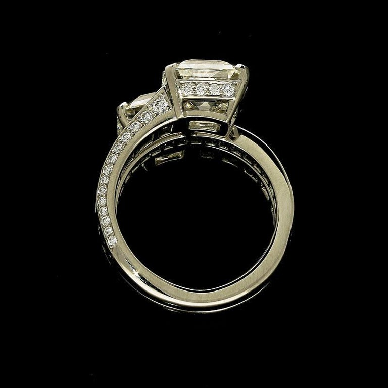 3.04ct J VS1 emerald cut diamond with GIA certificate  3.18ct I VVS2 emerald cut diamond with GIA certificate  3cts of calibre cut sapphires 0.65cts of round brilliant diamonds Platinum with maker's marks and London assay marks UK finger size L, can