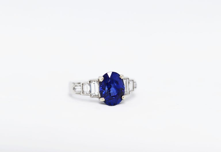 This beautiful Deco style, 1950's engagement ring features a royal blue oval sapphire weighing 3.18ct in a four claw open back setting. The sapphire is accompanied by two step baguette diamonds and a bullet cut diamond on each shoulder in rub-over,