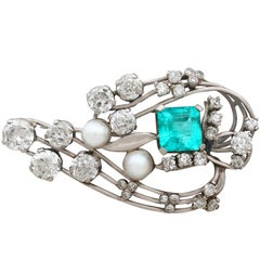 1920s Antique 3.19 Carat Emerald 4.38 Carat Diamond and Pearl Gold Brooch