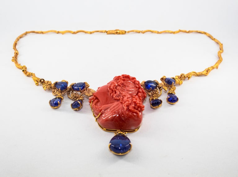 This Necklace is made of 14K Yellow Gold. This Necklace has 0.33 Carats of White Diamonds. This Necklace has 31.60 Carats of Tanzanite. This Necklace has Pink Carved Coral. The Girl made of Pink coral is Arianna, wife of Bacchus (Dionysus), she is