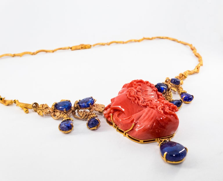Classical Greek 31.93 Carat Tanzanite White Diamond Pink Carved Coral Yellow Gold Greek Necklace For Sale