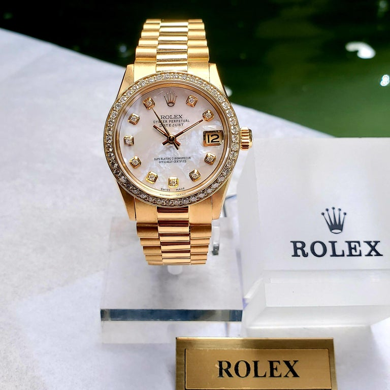 Stunning Rolex 31mm Midsize Datejust with Presidential link bracelet. This timepiece features a mother of pearl diamond dial and diamond bezel. Watch was reviewed and all necessary servicing was completed by a Rolex Authorized watchmaker. There is a