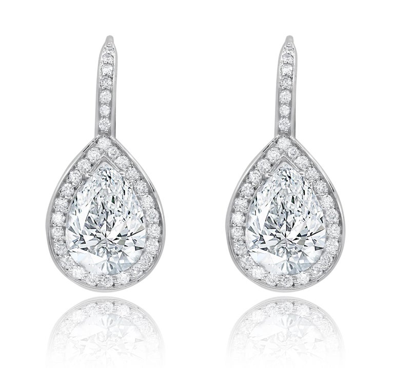 18 karat white gold hanging halo earrings feature 2.51 carats of pear shape diamonds, G-H in Color SI in Clarity surrounded by  0.70 carats of round brilliant cut diamonds.