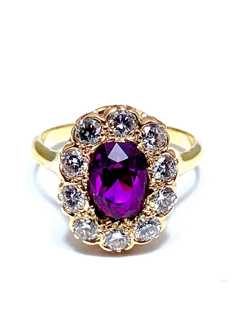 An absolutely eye catching purplish pink Sapphire and Diamond yellow gold ring.  The vibrant Sapphire is cushion shaped and weighs 3.21 carats.  It is set with a single row of 10 round brilliant diamonds weighing 0.80 carats.  The Sapphire has a
