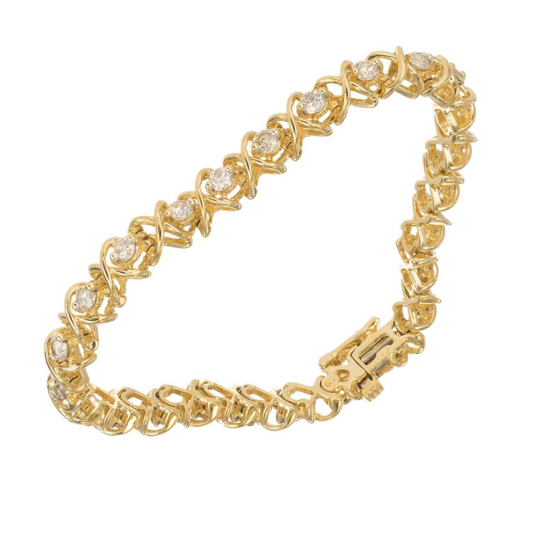 14k yellow gold and diamond tennis bracelet round brilliant cut diamonds are set alternating open X wires to appear as X's and O's  25 round I-J VS-SI diamonds 2.83-3.5mm Approximate 3.25 total weight 14k Yellow Gold Tested: 14k Stamped: