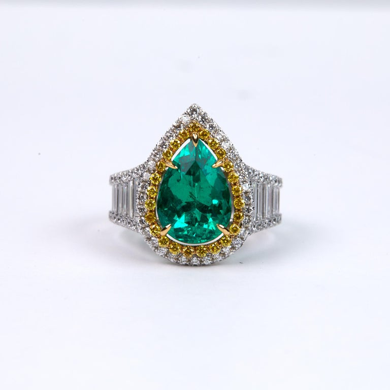 3.25 Carat Pear Shaped Natural Emerald and Diamond Ring. This one of a kind ring has 0.35 carats of Fancy Yellow Brilliant Round Diamonds that create a halo,  another .90 carats of F-G color, VS clarity Brilliant Round  shaped diamonds create a halo