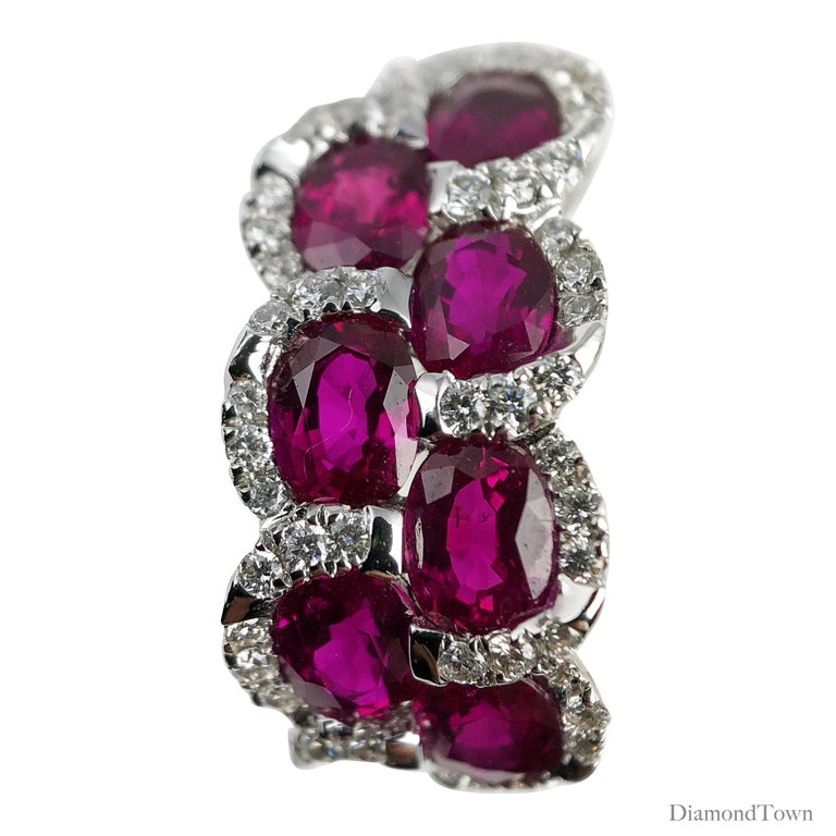 These lever-back earrings sparkle with seven oval cut rubies per earring (total weight 3.28 carats), nestled among a trail of round white diamonds (total diamond weight 0.39 carats). Set in 18k white gold.  Many of our items have matching companion