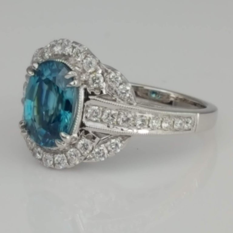 (DiamondTown) With a 3.34 carat oval cut blue zircon center, embellished by 0.61 carats round diamonds, this ring has a simple elegance suited for every occasion. Heart patterns in the decorated under gallery add a romantic touch.  Center: 3.34