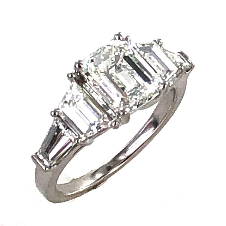 Gorgeous 2.02 carat emerald cut diamond engagement ring crafted with trapezoid and baguette cut side diamonds. The center 2.02 carat emerald cut diamond is graded by the GIA H color and SI1 clarity. The center is flanked by two trapezoid and two