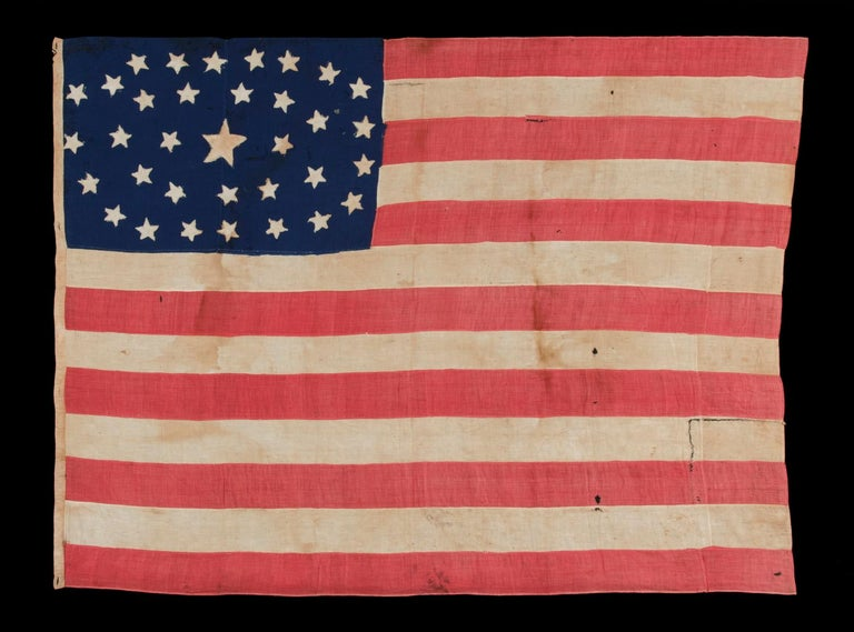 34 STARS IN AN OUTSTANDING OVAL MEDALLION CONFIGURATION, ON A NARROW CANTON THAT RESTS ON THE 6TH STRIPE, ON A HOMEMADE, ANTIQUE AMERICAN FLAG OF THE CIVIL WAR PERIOD, ENTIRELY HAND-SEWN, 1861-1863, KANSAS STATEHOOD:  34 star American national flag