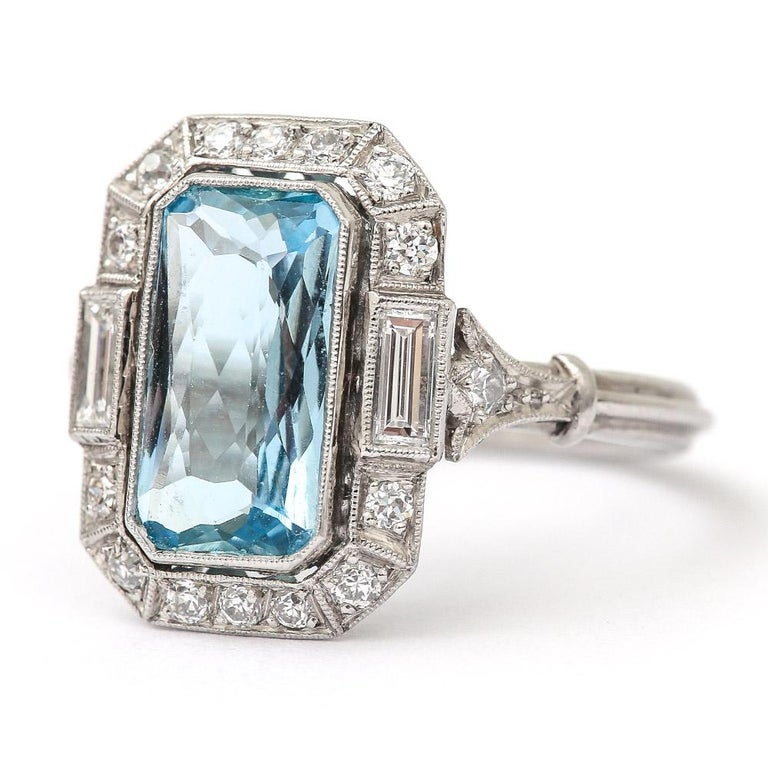 A super original Art Deco aquamarine and diamond ring set with a cushion cut, intricately faceted est. 3.40ct aquamarine flanked by two baguette diamonds (est. 0.20cts each). A further 14 brilliant cut diamonds estimated at 0.02cts each, all