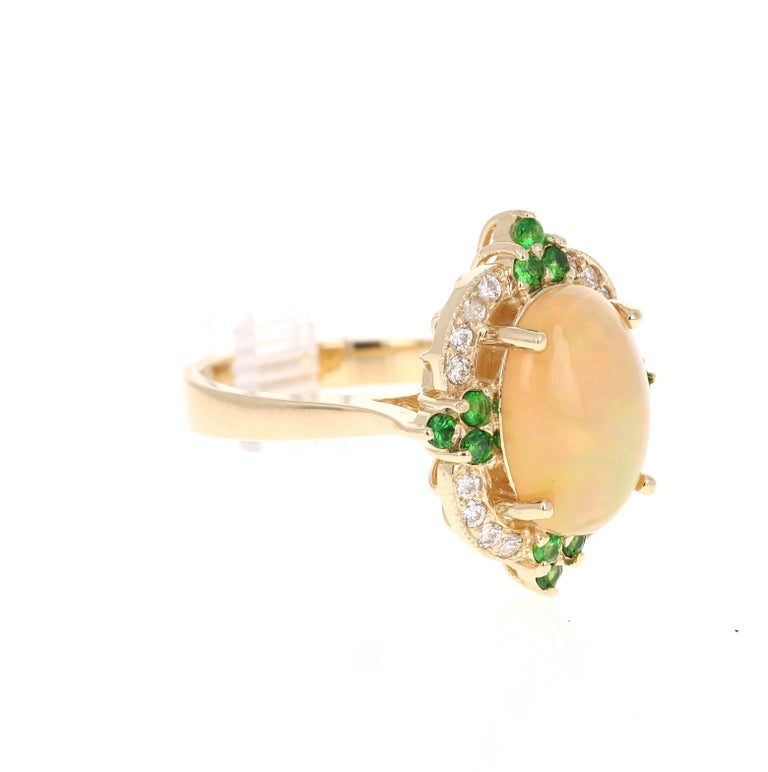 This gorgeous cocktail ring has a strinking Oval Cut Ethiopian Opal that weighs 2.78 Carats. The Opal measures approximately at 14 mm x 11 mm and has beautiful flashes of color in orange, green and yellow.   The ring also has 12 Round Cut Tsavorites