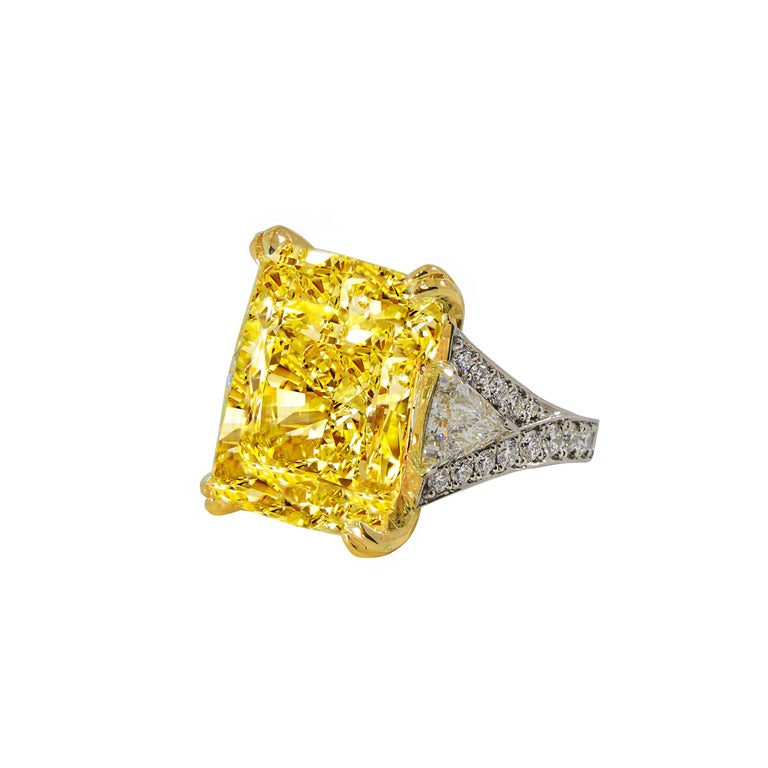 Magnificent radiant cut diamond ring is the Highlight of the Diana M. Jewels. Speechless 34.46 Carats Fancy Intense Yellow Radiant Cut  VS2 in clarity. Certified by GIA set with 3.20 Carats of two impressive trillion diamonds set in Platinum.