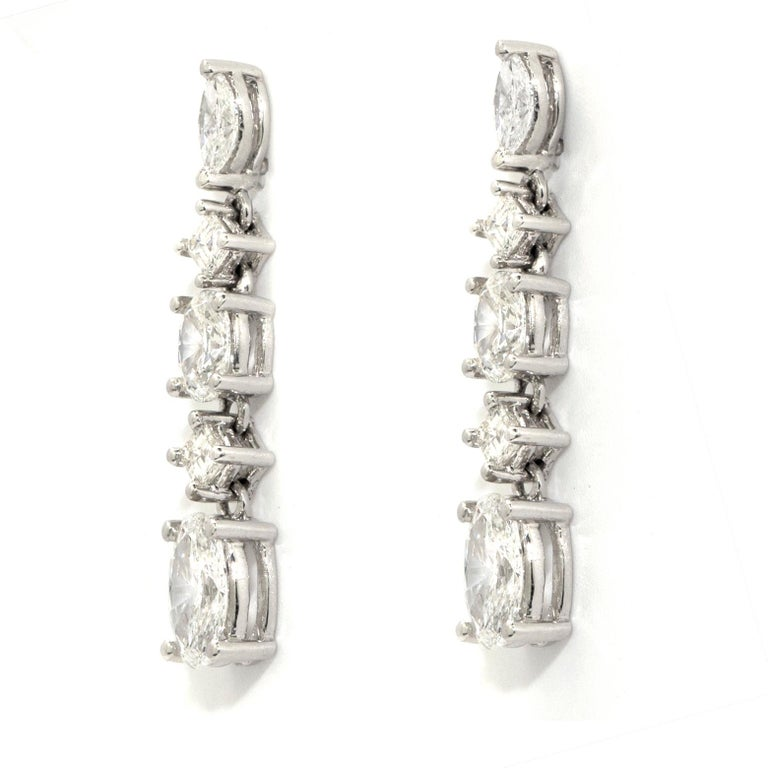 These beautiful 18 karat white gold dangling earrings features two oval diamonds of approximately 0.70ct each, two Asscher cut diamonds of approximately 0.35ct each and two marquize cut diamonds of approximately 0.20ct each.   4.45 grams 3cm