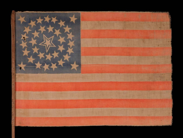 35 STARS IN A MEDALLION CONFIGURATION WITH A LARGE, HALOED CENTER STAR, ON ITS ORIGINAL WOODEN STAFF, CIVIL WAR PERIOD, WEST VIRGINIA STATEHOOD, 1863-65:  35 star American national parade flag, printed on cotton and retaining its original wooden