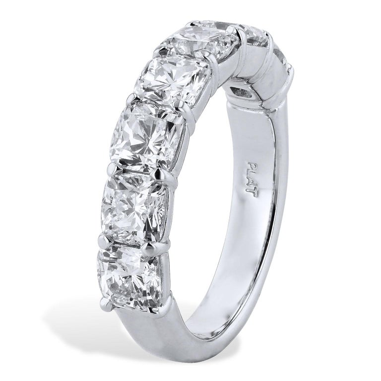 Seven cushion cut diamonds (H/VS2), with a total weight of 3.50 carats, are affixed to a platinum shank in a shared prong setting.  This ring provides a spectrum of light and color that glisters with pristine beauty in this buttercup eternity band
