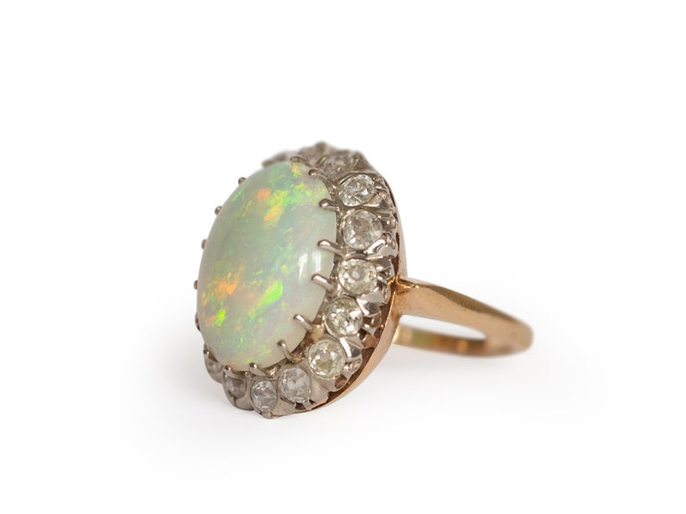Ring Size: 8.5 Metal Type: 14K Yellow Gold and White Gold Prongs [Hallmarked, and Tested] Weight: 5  grams  Diamond Details: Weight: 2.20 carat, total weight Cut: Old Mine Brilliant Color: I-J Clarity: SI  Opal Details: Weight: 3.50 carat Shape: