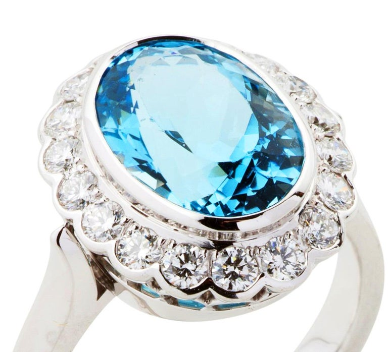 Handmade in 18 karat white gold is a 3.50 carat luscious blue oval cut Aquamarine. The bezel set centre stone has been surrounded by a scalloped halo of sparkling round brilliant cut diamonds, also bezel set, 18 total 0.60 carats of  F colour and VS