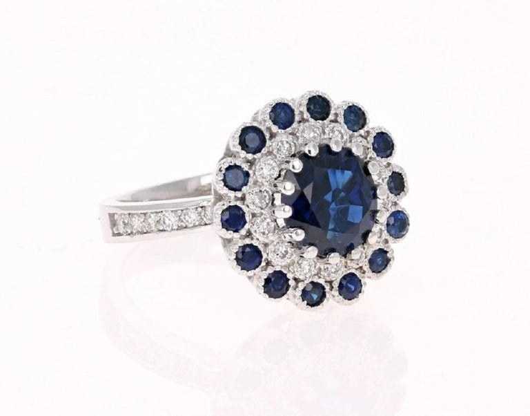 Gorgeous and Unique - truly a one of a kind piece designed by our in house talented designer!! This ring has a Round Cut Blue Sapphire that weighs 2.49 carats set in the center of the ring; this Sapphire measures at 8.5 mm. The Sapphire is