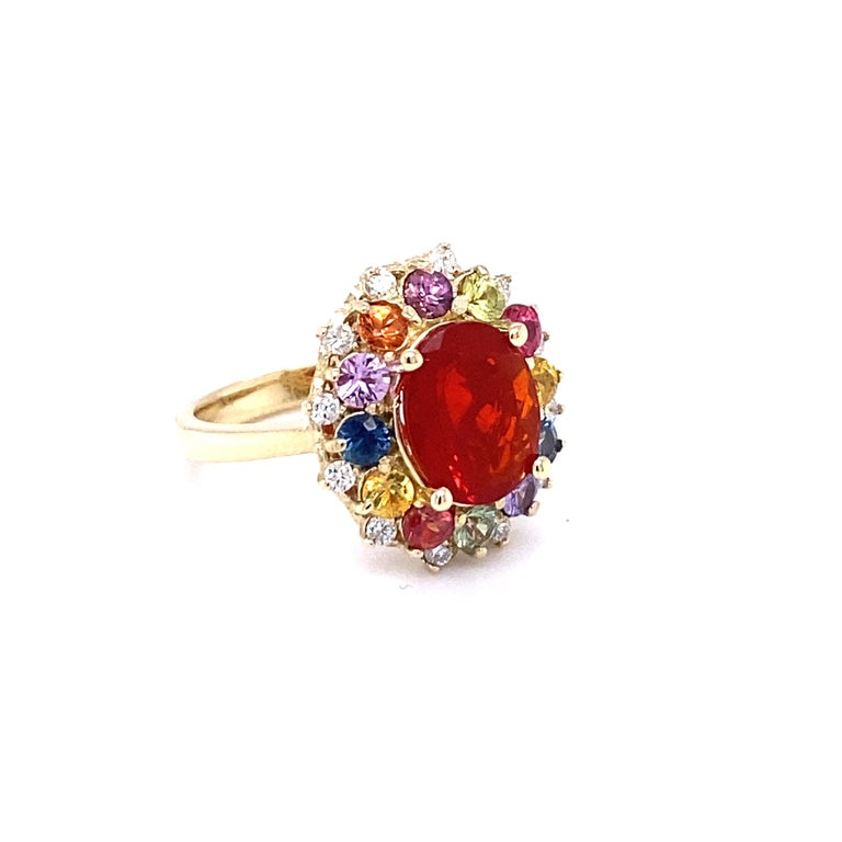 This Ring has a 2.06 carat Oval Cut Fire Opal as its center stone and is beautifully surrounded by 12 Multi-Colored Sapphires that weigh 1.52 Carats and 12 Round Cut Diamonds that weigh 0.26 carats (Clarity: SI2, Color: F)  The Total Carat Weight of