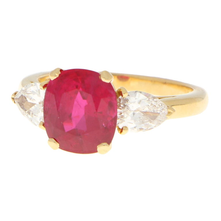 A truly stunning certificated Burmese ruby and diamond three stone engagement ring set in 18k yellow gold.  The ring is centrally set with a beautiful 3.58 carat hand-cut cushion shaped Burmese ruby which is securely four claw set in an elegant open