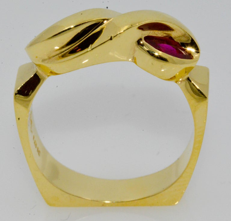 Twin marquise cut rubies peak out at either side of this sensational 18 karat yellow gold ring. The deep red rubies are .36 carat total weight, and bezel set. Created with a unique European shank, this captivating ring is not ordinary.
