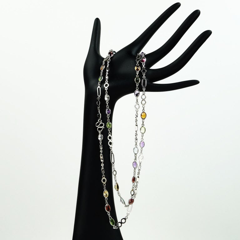 Necklace of Sterling Silver with bursts of oval faceted gemstones. 36 Inches in length is very versatile, this can easily be doubled. The gemstones include amethyst, citrine, peridot, and blue topaz.  See more from this designer by entering Gemjunky