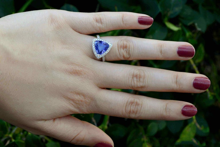 The Oceanside Modern Engagement Ring. At center stage, a triangle ( trillion ) Tanzanite of 3.60 carats, surrounded by a diamond halo and band. A most captivating, velvety, violet-blue gemstone with glimmering accents, you'll love the cool angles,
