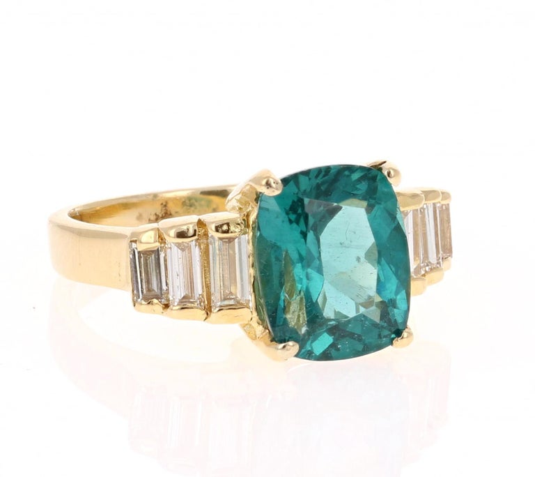 Classic and beautifully designed Apatite and Diamond Ring!  This ring has a 3.12 carat Cushion Cut Apatite in the center of the ring and is surrounded by 6 Baguette Cut Diamonds that weigh a total of 0.50 carats. The total carat weight of the ring