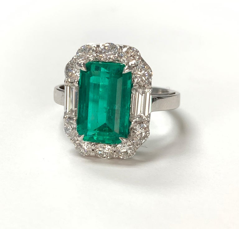 Gorgeously Green columbian emerald cut emerald and diamond ring hand crafted in 18k white gold.  The details are as follows :  Emerald weight : 3.63 Carat  Diamond weight :  Baguette diamond : 0.65 carat ( GH color and VS clarity )  Round diamond