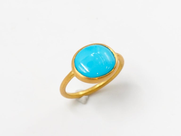 This simple ring by Scrives is composed of a large turquoise cabochon of 3.65 cts.  The stone is set in a 22kt closed gold setting. This turquoise is natural with a vibrant and strong colour. It has natural & typical small inclusions. The stone