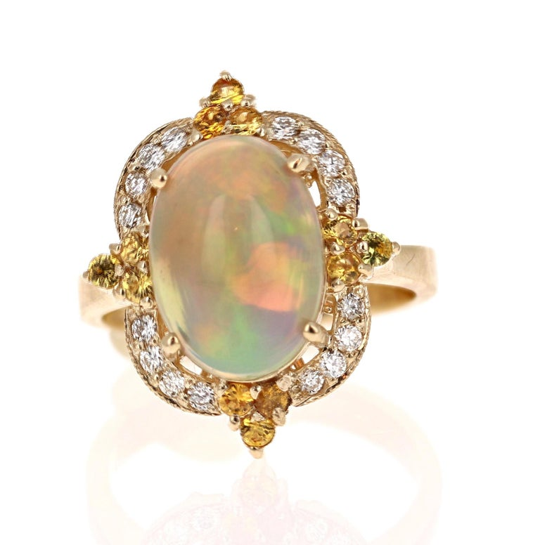 Opulent Opal, Yellow Sapphire and Diamond Ring in 14K Yellow Gold.  The beautiful Oval Cut, Ethiopian-Origin Opal with its striking flashes of color weighs 3.03 Carats. The Opal has flashes of color ranging from green, orange, yellow and red.   It