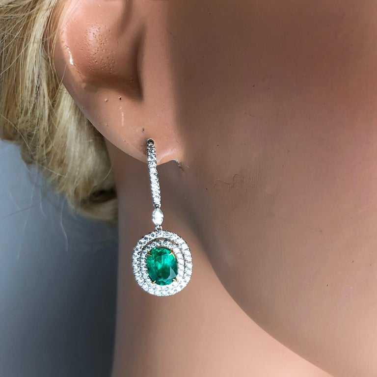 These beautiful drop dangle earrings feature 3.73 carats oval cut fine emerald, surrounded by double halos of round white diamonds. A single marquise cut diamond links the body of the earring to a lever-back hook, also featuring round white