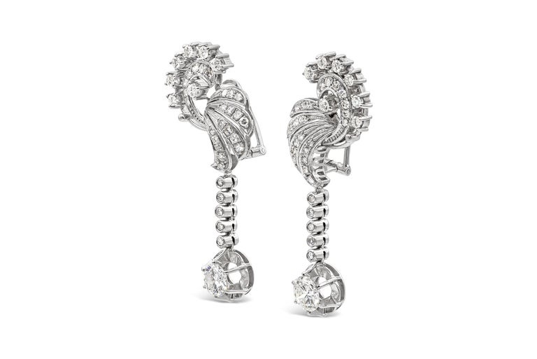 An intricately-designed pair of dangle earrings showcasing two round brilliant diamonds weighing 2.25 carats total. Suspended on an open-work design set with round brilliant and single cut diamonds weighing 1.50 carats total. Made in 18k white gold.