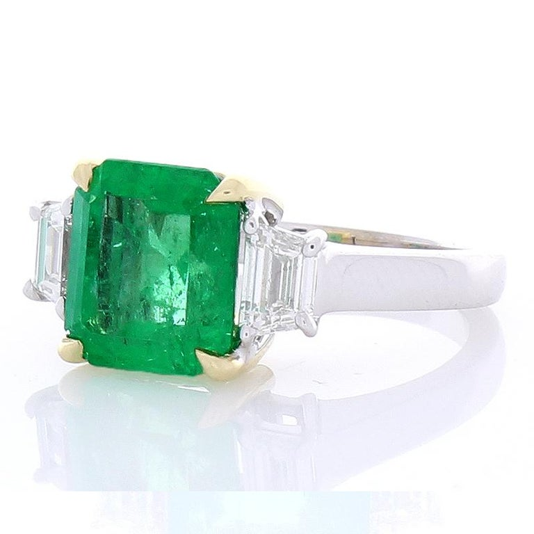 This is a three-stone ring that is timeless, classic, and richly unique. A 3.76 carat square octagonal cut green emerald is skillfully prong set in the center in shiny yellow gold accenting and measures 9.75x9MM. The gem source is Zambia; its color