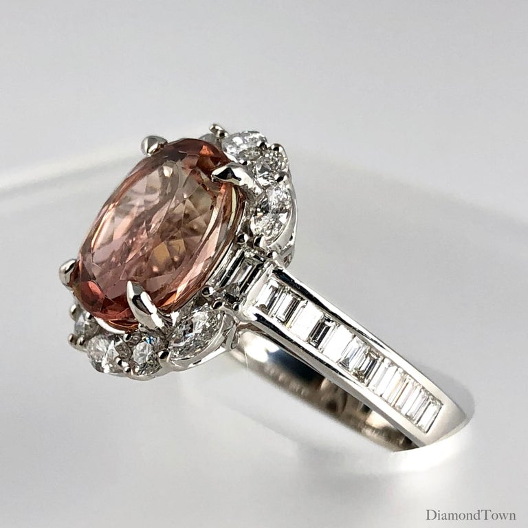 This stunning ring features a 3.76 Carat Oval Cushion Cut Orangy Pink Tourmaline center, surrounded by a halo of white diamonds. Additional baguette diamonds trail down the side shank, bringing the total diamond weight to 0.60 carats.  This ring can