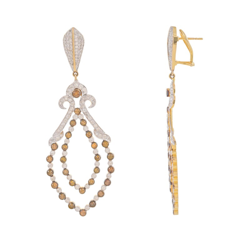 Discover these gorgeous earrings mounted in 18 karats gold featuring 56 fancy color diamonds weighing approximately 3.77 carats in total within an openwork diamond-set frame of foliate design to a diamond set surmount weighing approximately 3.09