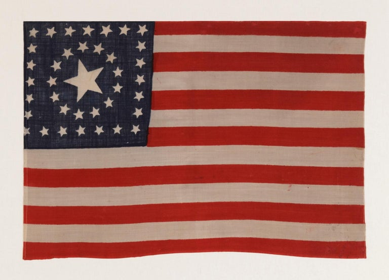 38 STARS IN A RARE CIRCLE-IN-A-SQUARE MEDALLION WITH A HUGE CENTER STAR, MADE FOR THE 1876 CENTENNIAL INTERNATIONAL EXPOSITION BY HORSTMANN BROS. IN PHILADELPHIA   38 star American national parade flag, press-dyed on wool bunting, with an especially