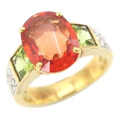 3.86 Carat Oval Orange Sapphire Diamond Pavé Ring Flanked with Square Peridots
