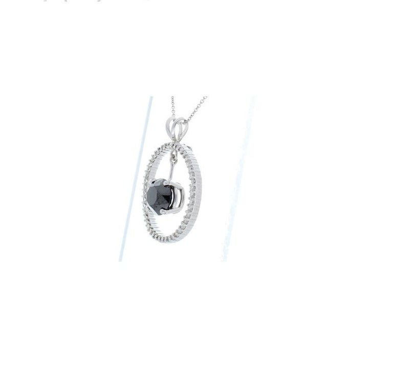 This necklace is total diamond suspension. An 8.87 carat brilliant cut black diamond floats in the center of a glowing 0.67 carat circle of 45 brilliant cut diamonds, hung from a delicate 14 K white gold setting with a classic split bail. The