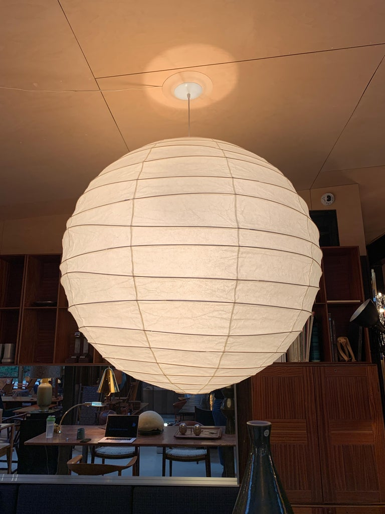 A hanging round Akari lighting sculpture and lantern, handcrafted from washi paper and bamboo ribbing. Designed by Isamu Noguchi in 1951 and manufactured in Gifu, Japan. Measures: 39