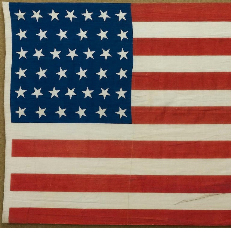 This is a 39-star unofficial American flag, handmade and printed on cotton. The flag dates to 1889 and has a unique history, thanks to its rare star-count.  The flag's canton is printed in a deep royal blue, with 39 five-pointed white stars. The